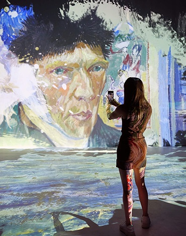 young woman taking a picture of Van Gogh self portrait